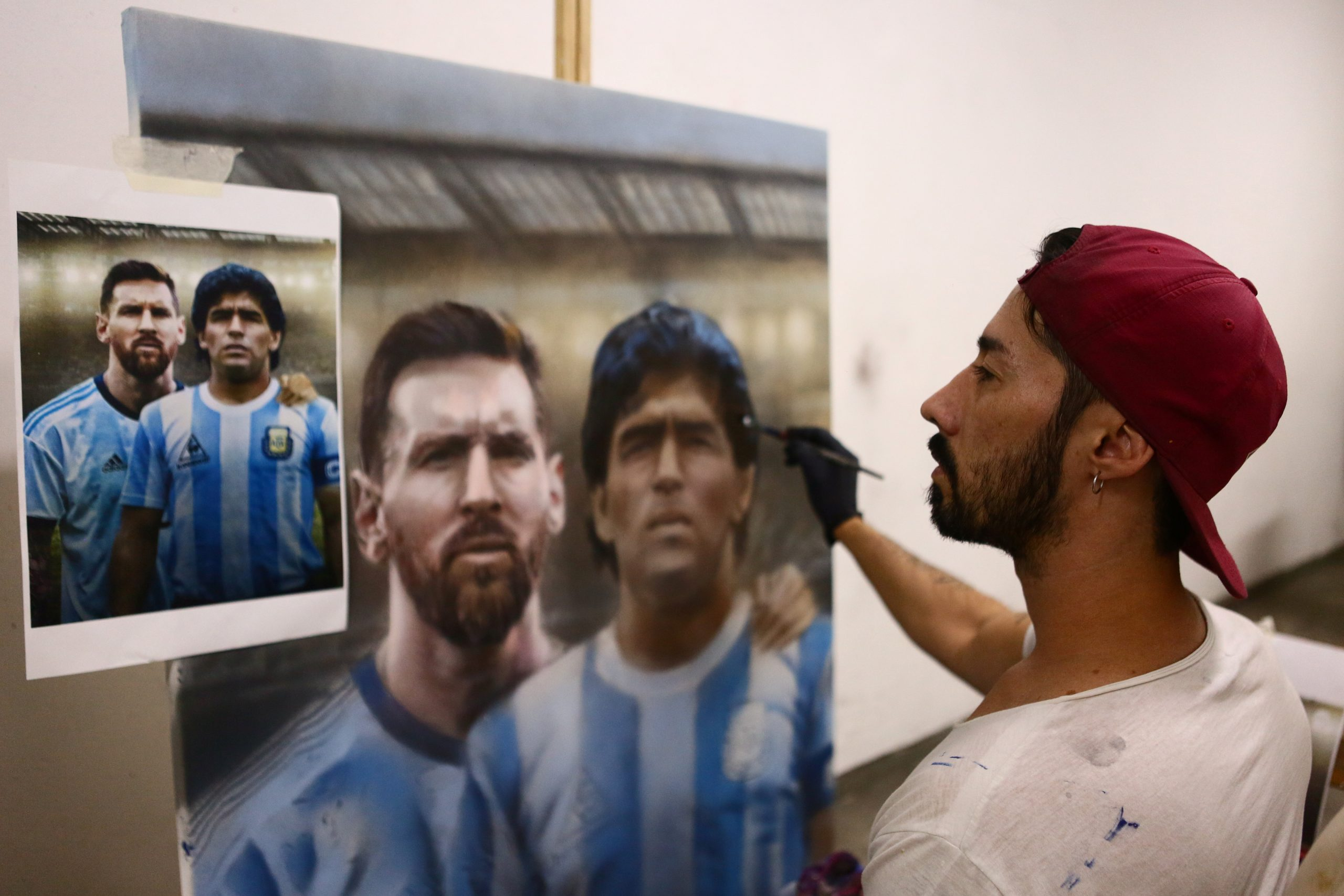 Pedestrians take a picture next to paintings made by Argentine artist Maximiliano Bagnasco of soccer legend Diego Armando Maradona, in Buenos Aires, Argentina April 14, 2021. Picture taken April 14, 2021. REUTERS/Matias Baglietto